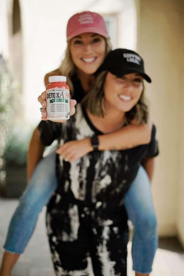 Sirena Salvante on Tamrin Olden's back, holding a bottle of Detoxathin