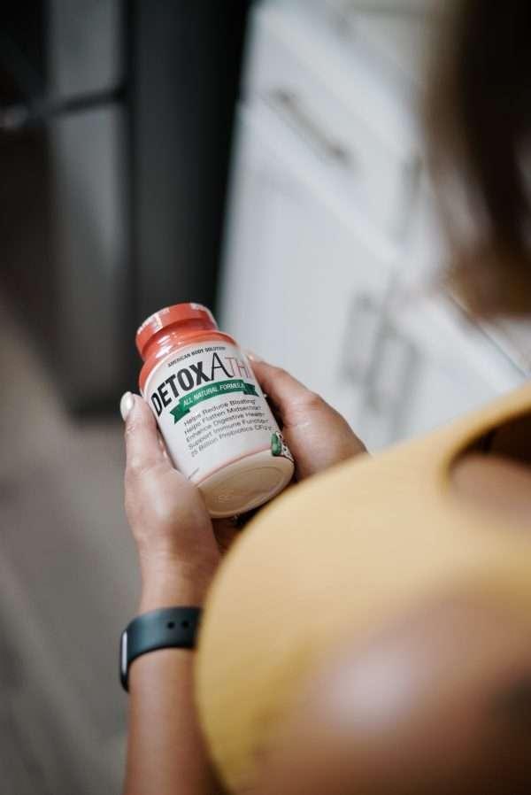 Woman Holding A Bottle Of Detoxathin